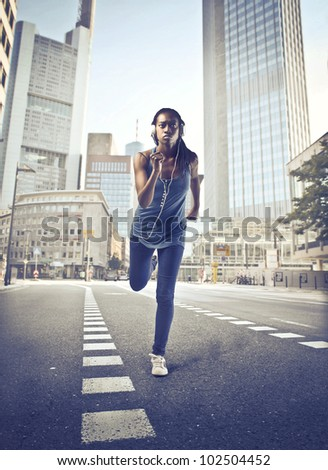 Beautiful young african woman jogging on a city street