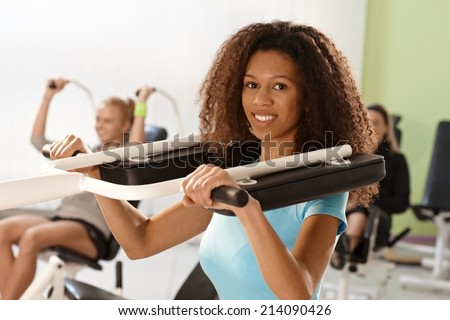 Beautiful young afro woman training at gym using weight machine, smiling. - stock photo