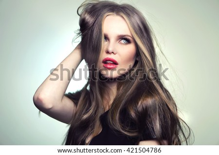 Beautiful young and emotional caucasian woman model with great hair and makeup, red lips and deep blue eyes - posing at studio in the softbox and light flashes.