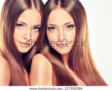 Beautiful young and fresh girl twins , with long shiny healthy hair - stock photo