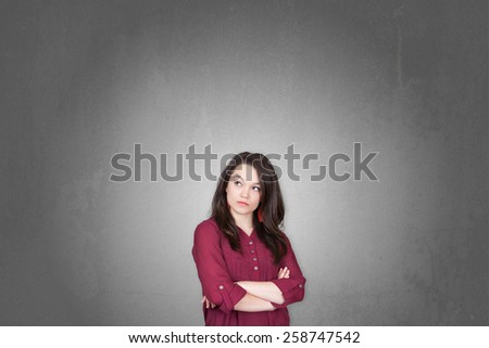 Beautiful young and pretty woman wondering for something in front of old grey wall - stock photo