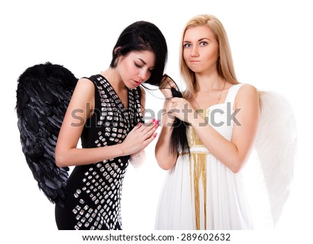 Beautiful young angel pulls black angel's hair isolated over white background - stock photo