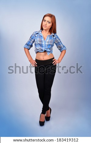 Beautiful young arab woman posing with hands on hips isolated on blue background - stock photo