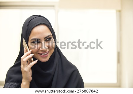 beautiful young arabian woman talking on cell phone - stock photo