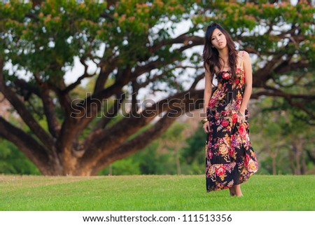 Beautiful young asia  woman in color dress posing outdoor - stock photo