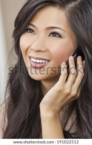 Beautiful young Asian Chinese woman or girl in her twenties talking on a smart cell phone - stock photo