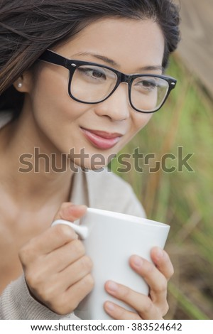 Beautiful young Asian Chinese woman or girl wearing glasses, outside, smiling and drinking a cup of coffee or tea - stock photo