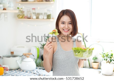 Beautiful young asian girl eating salad. smiling happy girl eating healthy food.