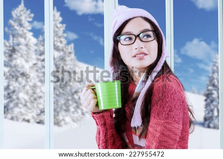 Beautiful young asian girl wearing warm clothes while drinking hot beverage at home in winter day - stock photo