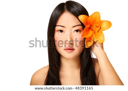 Beautiful young asian girl with bright flower in hand, on white background