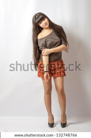 Beautiful young asian model. Studio shot. Cheerful young Asian girl, half length (torso shot) closeup portrait on white background. - stock photo