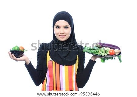Beautiful young asian muslim woman holding vegetables and smile while looking to the camera in the kitchen isolated white background - stock photo