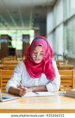 Beautiful young asian muslim woman working with files and laptop.