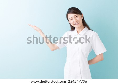 Beautiful young asian nurse to recommend it to - stock photo
