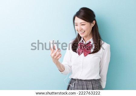 Beautiful young asian school girl to see a smart phone - stock photo