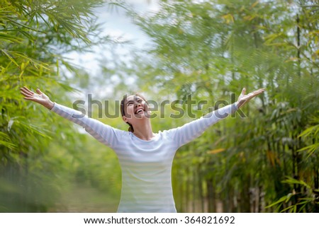 Beautiful Young Asian Woman Enjoying Nature. Healthy Smiling Girl in Green Bamboo Forest. - stock photo