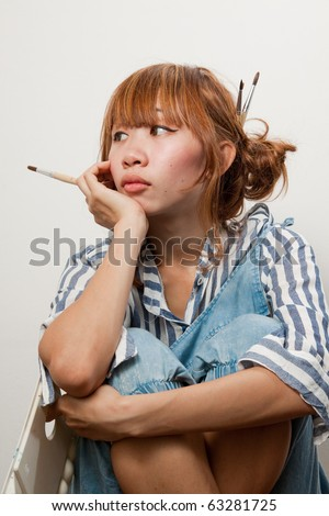Beautiful young asian woman holding paintbrush looking pensive isolated over white background.