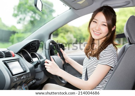 Beautiful young asian woman in a car - stock photo