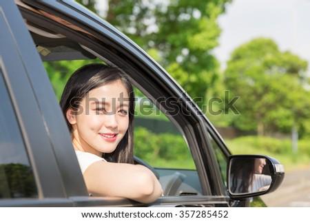 Beautiful young asian woman in a car - stock photo