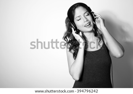 beautiful young asian woman listening to music with headphones - stock photo