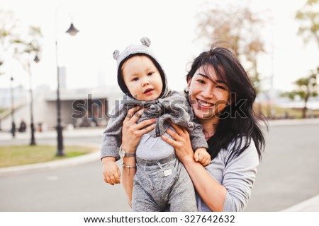 Beautiful young asian woman mom with freckles and her son relaxing outdoors. Mother brunette with dark hair holds her blond son. Son wearing bear costume. Unusual appearance and heredity concept - stock photo
