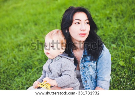 Beautiful young asian woman mom with freckles and her son relaxing outdoors. Mother brunette with dark hair and her son is blond. Unusual appearance, diversity and heredity concept. Copy space  - stock photo