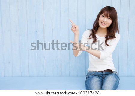 Beautiful young Asian woman pointing with space for copy - stock photo