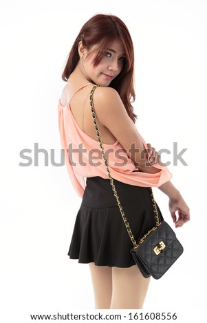 Beautiful young asian woman posing in singlet top with black mini skirt isolated on white background.