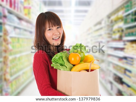 Beautiful young Asian woman shopping in a grocery store/supermarket . - stock photo