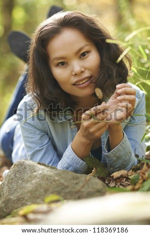 Beautiful young Asian woman sitting alone at rustic outdoor setting on sunny day.