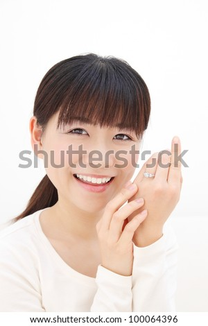 Beautiful young Asian woman slip a ring on the finger - stock photo