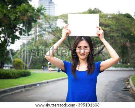Beautiful Young Asian woman standing in the park, holding up a blank sign above her head with copy space (selective focus with blurry background) - stock photo