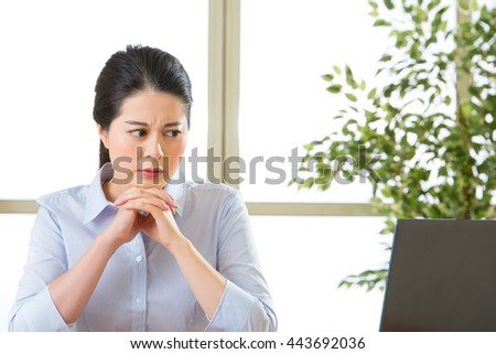 Beautiful young asian woman thinking with headache in office - stock photo