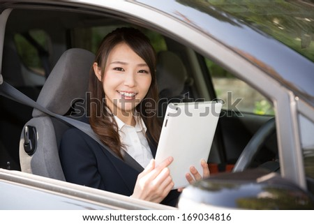 Beautiful young asian woman using tablet computer in a car - stock photo