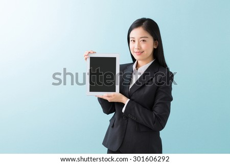 Beautiful young asian woman who shows the screen of the tablet computer - stock photo