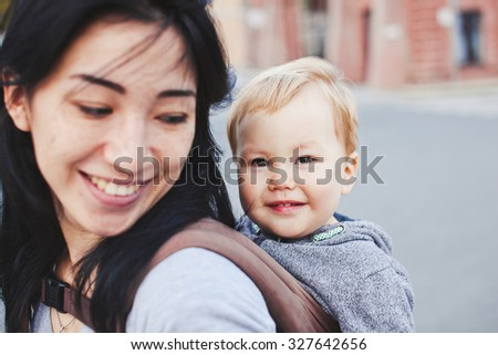 Beautiful young asian woman with freckles and her son relax outdoors. Mother brunette with dark hair and her son is blond. Unusual appearance and heredity concept. Baby sits in sling on mothers back - stock photo