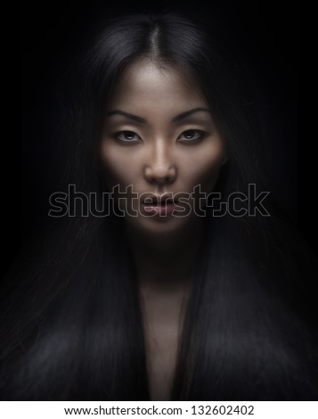 Beautiful young asian woman with long hair on dark background - stock photo