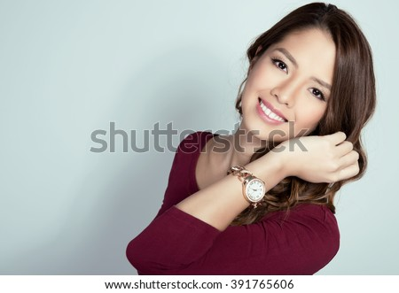 beautiful young asian woman with long hair posing in casual clothes and wearing a wrist watch - stock photo