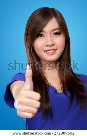 Beautiful young Asian woman with thumbs up gestures, on vibrant blue background - stock photo