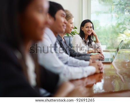 Beautiful young asian woman working and smiling at camera during business meeting with colleagues.