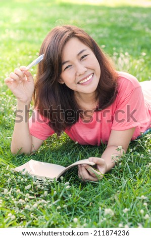 Beautiful young asian woman writing in her notebook on the meadow with white flowers