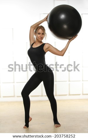 Beautiful young attractive beautiful woman with blond hair standing holding up ? ball for fitness black dressed up in black suit elastic doing gymnastics aerobics fitness yoga relaxes meditates - stock photo