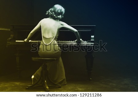 Beautiful young attractive woman in evening dress and piano - stock photo