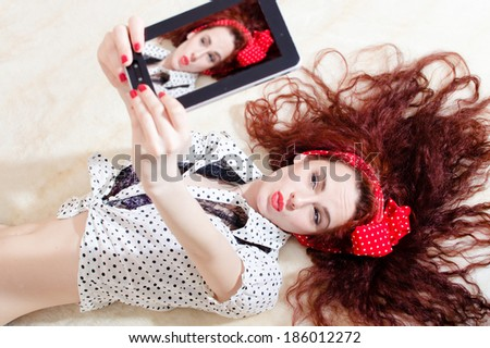beautiful young attractive woman pinup girl lying and taking selfy or ...