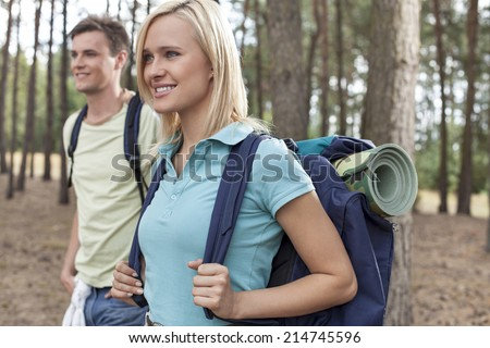 Beautiful young backpacker with man trekking in forest - stock photo