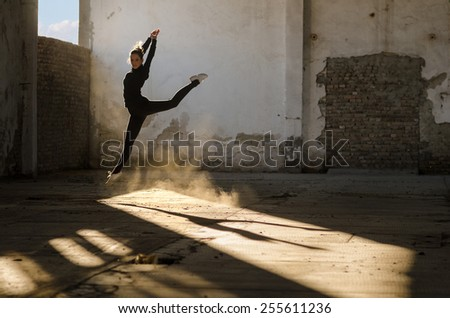 Beautiful young ballerina dancing in abandoned building. - stock photo