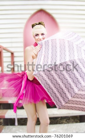 Beautiful Young Ballerina Woman In Pink Lace Tutu Holding A Umbrella Poses In Front Of The Steps Of A Church Door In A Rain Dance Representation - stock photo
