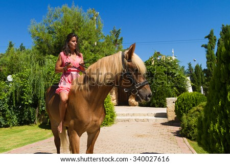 Beautiful young barefoot modern brunette amazon with red dress, riding a slender brown-blond purebred horse without a saddle.