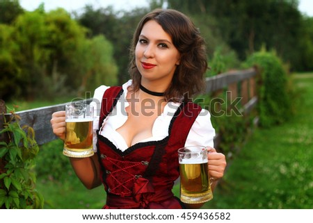Beautiful, young, Bavarian woman in dirndl holding oktoberfest beer stein. Close-up