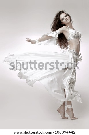 Beautiful young belly dancer wearing white dress - stock photo